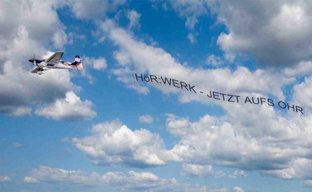 Flugzeug mit Banner am HImmel