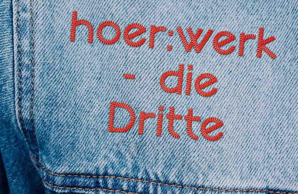 auf eine Jeansjacke sind die Wörter Hörwerk, die Dritte gestickt