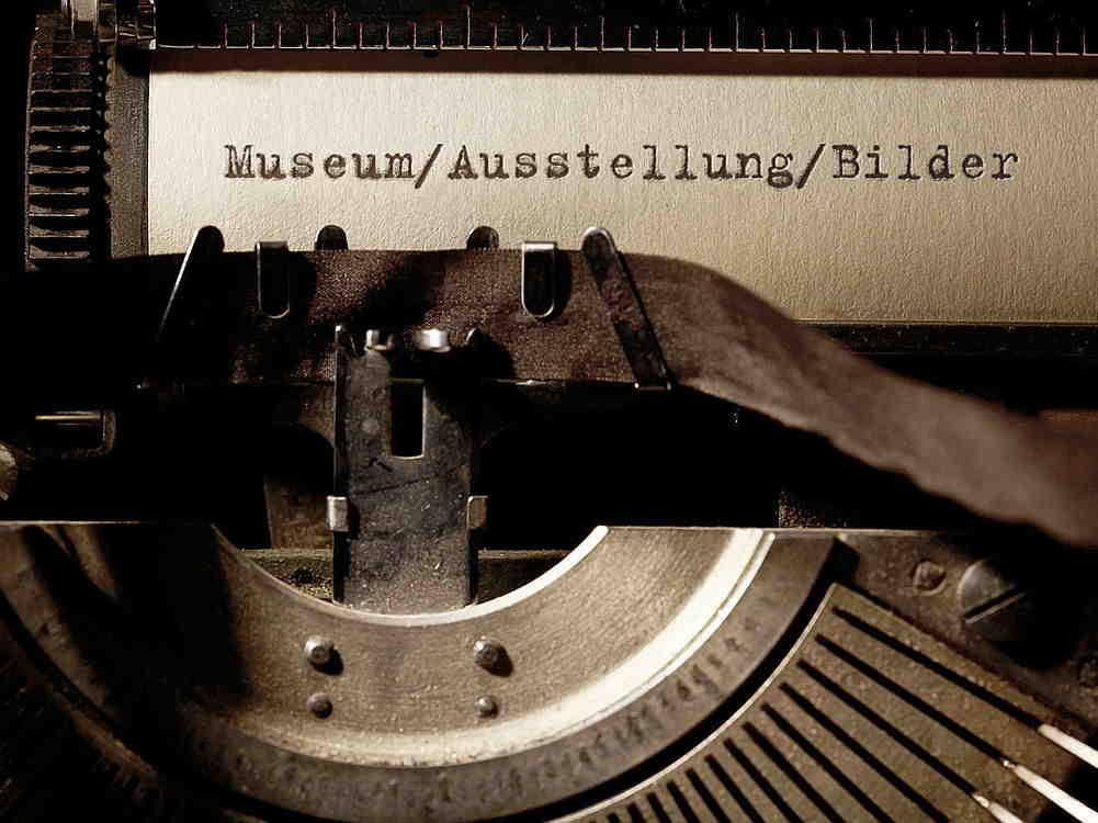 Auf einer alten Schreibmaschine ist ein Papier eingespannt, auf dem stehen die Wörter Museum, Ausstellung und Bilder